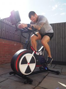 Chris is in his garden on a static exercise bike, cycling hard in the sun