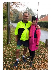 Abbie and her dad are stood outside after a run, Abbie is wearing a hat that is a flamingos head. They look tired and happy post run.