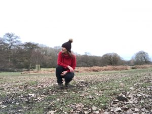 Sandra is outside in a field during winter, with dead leaves around her and bare trees in the background, she is crouched down and wearing a bobble hat and red jumper.