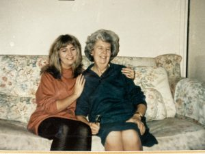 a photo of Sally and her mum sat down on a sofa, Sally has her arm round her mums shoulder and they are both smiling